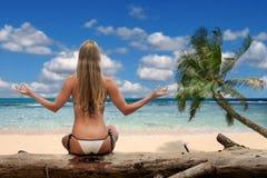 Mujer hermosa en un bikiní meditating en el beac Fotos de archivo
