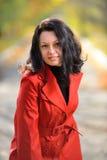 Mujer hermosa en un capote rojo Fotografía de archivo libre de regalías