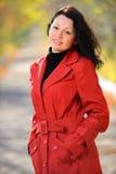 Mujer hermosa en un capote rojo Imágenes de archivo libres de regalías