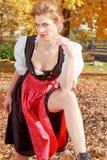 Mujer hermosa en un dirndl en un parque del otoño Foto de archivo libre de regalías