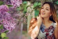 Mujer hermosa en un jardín de la primavera con las lilas florecientes imágenes de archivo libres de regalías