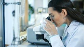 Mujer hermosa en un laboratorio que trabaja con un microscopio almacen de metraje de vídeo