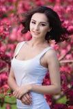 Mujer hermosa en un parque con las flores rosadas foto de archivo