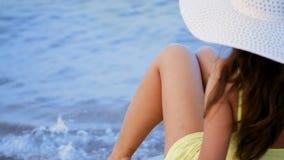 Mujer hermosa en un sombrero blanco grande que toma el sol en un deckchair metrajes