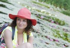 Mujer hermosa en un sombrero y lago con los lirios de agua Imágenes de archivo libres de regalías