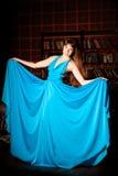 Mujer hermosa en un vestido azul largo en el interior rico Joven Imagenes de archivo