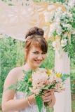 Mujer hermosa en un vestido de boda en un photozone adornado con las flores frescas, la presentación y el retrato Fotos de archivo libres de regalías