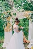 Mujer hermosa en un vestido de boda en un photozone adornado con las flores frescas, la presentación y el retrato Fotos de archivo