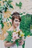 Mujer hermosa en un vestido de boda en un photozone adornado con las flores frescas, la presentación y el retrato Imagenes de archivo