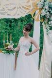 Mujer hermosa en un vestido de boda en un photozone adornado con las flores frescas, la presentación y el retrato Imagen de archivo libre de regalías
