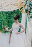 Mujer hermosa en un vestido de boda en un photozone adornado con las flores frescas, la presentación y el retrato Fotografía de archivo libre de regalías