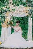 Mujer hermosa en un vestido de boda en un photozone adornado con las flores frescas, la presentación y el retrato Fotografía de archivo