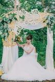 Mujer hermosa en un vestido de boda en un photozone adornado con las flores frescas, la presentación y el retrato Imágenes de archivo libres de regalías