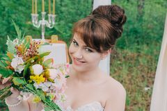 Mujer hermosa en un vestido de boda en un photozone adornado con las flores frescas, la presentación y el retrato Imagen de archivo