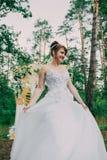 Mujer hermosa en un vestido de boda en un photozone adornado con las flores frescas, la presentación y el retrato Foto de archivo libre de regalías