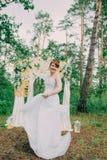 Mujer hermosa en un vestido de boda en un photozone adornado con las flores frescas, la presentación y el retrato Foto de archivo