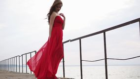 Mujer hermosa en un vestido que se coloca cerca del mar, ella parece pensativa y romántica almacen de video