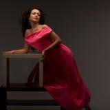 Mujer hermosa en un vestido rosado largo foto de archivo