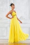 Mujer hermosa en una alineada amarilla larga. Foto de archivo libre de regalías