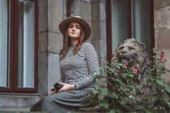 Mujer hermosa en una camisa rayada y un sombrero Sostiene la cámara cerca de la estatua de un león contra la perspectiva del viej foto de archivo