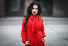 Mujer hermosa en una capa roja imagenes de archivo