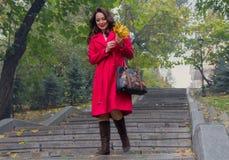 Mujer hermosa en una capa roja que camina abajo de las escaleras Fotos de archivo libres de regalías