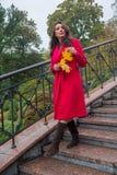 Mujer hermosa en una capa roja que camina abajo de las escaleras Foto de archivo