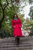 Mujer hermosa en una capa roja que camina abajo de las escaleras Foto de archivo libre de regalías