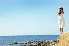 Mujer hermosa en una playa del mar en guantes negros imagen de archivo libre de regalías