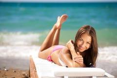 Mujer hermosa en una playa en un salón de la calesa Imagen de archivo