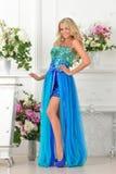 Mujer hermosa en vestido azul en interior de lujo. fotografía de archivo