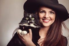 Mujer hermosa en vestido y sombrero negros con el gato Foto de archivo libre de regalías