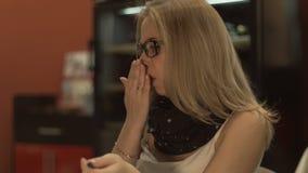 Mujer hermosa en vidrios en la mesa y toser mientras que trabaja en el ordenador portátil metrajes