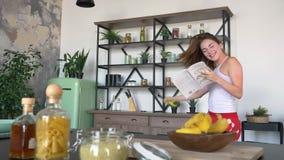 Mujer hermosa encantadora con el pelo del jengibre que lee el libro culinario y que baila en cocina moderna, teniendo buen tiempo almacen de metraje de vídeo