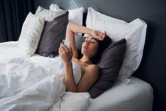 Mujer hermosa enferma que miente en cama con alta fiebre Frío, gripe, fiebre y jaqueca con un termómetro y un teléfono fotos de archivo
