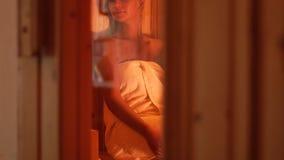 Mujer hermosa envuelta en la toalla de baño que toma sauna en salón del balneario de la belleza Mujer de relajación que goza de l almacen de metraje de vídeo