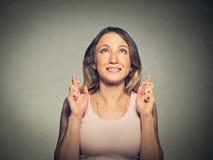 Mujer hermosa esperanzada que cruza sus fingeres que miran para arriba que esperan Fotografía de archivo libre de regalías