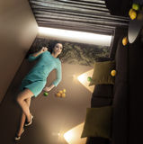 Mujer hermosa extraordinaria que miente y que se relaja en la pared en el cuarto volcado con los limones Imagen de archivo