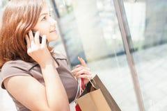 Mujer hermosa feliz con el bolso usando el teléfono móvil, centro comercial Imágenes de archivo libres de regalías