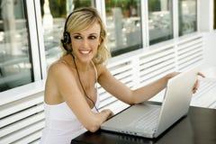 Mujer hermosa feliz con la computadora portátil y el receptor de cabeza Fotografía de archivo