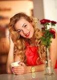 Mujer hermosa feliz en casa en la tabla con la taza de café Fotografía de archivo libre de regalías