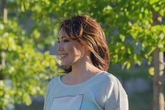 Mujer hermosa feliz en el jard?n foto de archivo