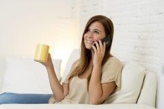 Mujer hermosa feliz en el sofá que habla en la sonrisa relajada y alegre del teléfono móvil en casa sofá Imagenes de archivo