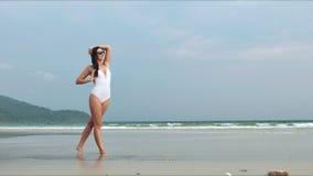 Mujer hermosa feliz en el traje de baño blanco que presenta en la playa tropical metrajes