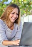 Mujer hermosa feliz hojeando su ordenador portátil al aire libre Imágenes de archivo libres de regalías