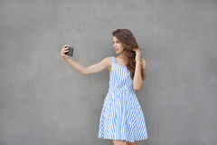 Mujer hermosa feliz joven en vestido ligero con el pelo rizado moreno largo que presenta contra la pared que hace la foto del sel Imagenes de archivo