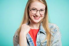 Mujer hermosa feliz joven que mira la cámara Muchacha que sonríe en un fondo azul Imágenes de archivo libres de regalías