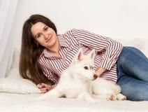 Mujer hermosa feliz que descansa sobre un sofá con su animal doméstico muchacha que abraza el perro esquimal del perrito Foto de archivo libre de regalías