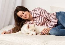 Mujer hermosa feliz que descansa sobre un sofá con su animal doméstico muchacha que abraza el perro esquimal del perrito Fotos de archivo