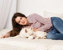 Mujer hermosa feliz que descansa sobre un sofá con su animal doméstico muchacha que abraza el perro esquimal del perrito Imágenes de archivo libres de regalías